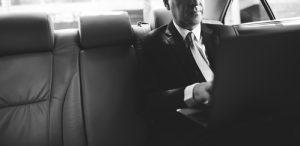 Businessman Using Laptop Car Inside